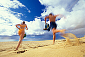 Couple running on the beach, blurred motion
