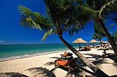 People sunbathing on a palm beach, Bali Hyatt Hotel beach, Bali, Indonesia