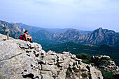 Woman sitting near cross, hiking route GR 20, Bavella Pass, Corsica, France