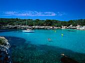 People swimming in the bay at Cala Turqueta, Minorca, Spain