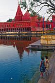 People and water basin in front of Durga temple, Varanasi, Benares, Uttar Pradesh, India, Asia
