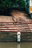 Praying pilgrim standing on stairs at the river Ganges, Ghat, Varanasi, Uttar Pradesh, India