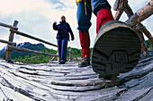 Couple hiking over bridge, Dumdalen, Jotunheimen NP, Western Middle Norway