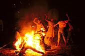 Young pilgrims dancing Sevillanas beside a campfire at night, Romería al Rocío, El Rocío, pilgrimage, Andalusia, Spain