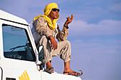 Chauffeur sitting on a jeep, Jeep Tour, Salt Desert, Chott el Djerid, Tunesia