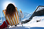 Woman in deck chair, St. Christoph, Woman with drink sitting on deck chair in the snow, St. Anton at Arlberg, Tyrol, Austria