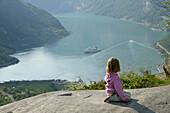 Girl sitting on the rocks above Geiranger Fjord, More og Romsdal, Norway