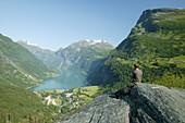 Man sitting on rocks above Geiranger Fjord enjoying the view, More og Romsdal, Norway