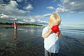 Two children playing on the beach at Toensberg, Vestfold, Oslofjord, Norway