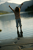 Child with outstretched arms on the beach at lake vaga, near Lom, Oppland, Norway