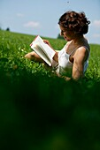 Young Woman reading book on lawn, bavaria Germany