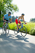 Young couple riding fitness bikes, Bavaria, Germany