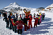 Ski kids with instructor doing a warm up before skiing lessons, Wirl near Galtuer, Tyrol, Austria
