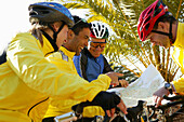 Group of cyclists looking at map, Cala Santanyi, Majorca, Balearic Island, Spain