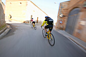 People on a cycle tour passing Santanyi village, Majorca, Balearic Islands, Spain