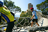 People on a cycle tour pushing their bikes from Torre Ses animes, Majorca, Balearic Islands, Spain