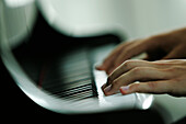 Man playing piano, close-up hands, Germany