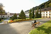 Nun sitting on a bench, Ettal Abbey, Ettal, Bavaria, Germany