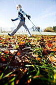 Young woman Nordic Walking through Autumn leaves, Voralpenland, Oberambach, Lake Starnberg, Bavaria, Germany