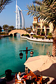 People in a restaurant at the canal and the Burj al Arab hotel, Dubai, United Arab Emirates, Middle East, Asia