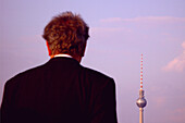 Man infront of television tower, berlin, germany