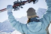 Woman holding skis, Kuehtai, Skifahrerin, Hohe Mut und Gaiskogel im Hintergrund, Kuehtai, Tyrol, Austria