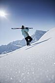 Woman walking through snow, holding skis, Hohe Mut and Gaiskogel in backround, Kuehtai, Tyrol, Austria