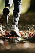 Man running through a puddle, Voralpenland, Germany