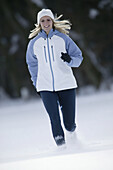 Young woman running on snow