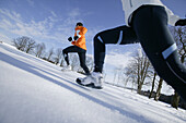 Young couple running on snow