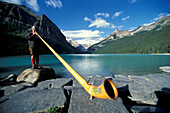 Man blowing an alp horn at Lake Louise, Rocky Mountains, Alberta, Canada