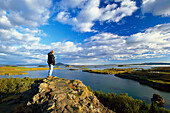 Man standing on a rock looking at the view, Myvatn, North Island, Island