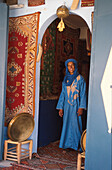 Ibrahim, Berber standing at the entrance to a house wearing traditional clothing, Berber Apartment with Hand of Fatima, Tafraoute, Anti-Atlas, Marocco