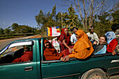 Travelling monks and Burmese, laughing monks and locals travelling in a pickup to a temple celebration Moenche und andere Burmese im Pickup