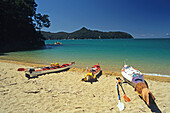 Kayaks on the beach in the sunlight, Abel Tasman Coast Track, Abel Tasman National Park, New Zealand, Oceania
