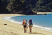 Hikers with rucksack on the beach in the sunlight, Abel Tasman Coast Track, Abel Tasman National Park, New Zealand, Oceania