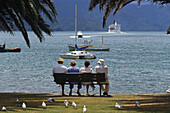 Tourists sitting on bench Picton waterfront, tourists watch Cook Strait Ferry departing in the distance, at Picton in the north of the South Island