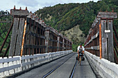 Cyclist on wooden bridge, traffic and railway sharing the narrow bridge, West Coast, South Island, New Zealand, Oceania