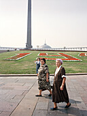 Two women in front of war memorial at Victory Park, Moscow, Russia