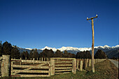 View of weathered fence in front of snow covered Southern Alps, West Coast, South Island, New Zealand, Oceania