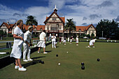Ladies in white uniforms playing lawn bowls in front of old spa, Rotorua, North Island, New Zealand
