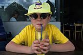 Portrait, young boy in yellow in cafe, Junge im Sonnenbrille und gelb trinkt Saft, boy with New Zealand cap drinking through straw, sunglasses