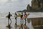 Surfers with surfboards, Piha surf beach, beach famous for surfing, west coast near Auckland, North Island, New Zealand