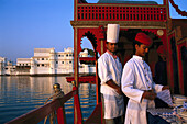 Cook and waiter on restaurant boat of Lake Palace Hotel, Lake Pichola, Udaipur, Rajasthan, India, Asia