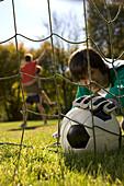 Goalkeeper fetching back soccer ball