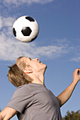 Young soccer player exercising headers