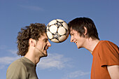 Two young man juggling soccer ball between their heads