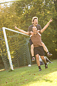 Young male soccer players jubilating, arms wide open