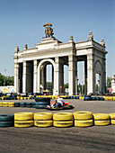 Man driving a go-kart in front of a main entrance to All-Russia Exhibition Centre, Moscow, Russia