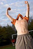 Young male soccer player jubilating, lifting t-shirt